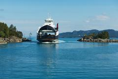 Ferry boat arrives to the port in Tveit, Norway. Stock Photos