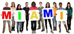 Group of young multi ethnic people holding word Miami Stock Photos