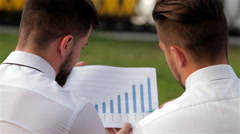 Two partners analyzing bar chart - stock footage