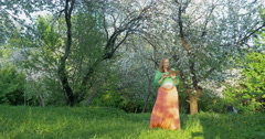 Pregnant woman with tablet PC walking in bloomy park Stock Footage