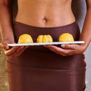 Dessert in hand at level of the abdomen - stock photo