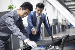 Auto mechanic talking with car owner Kuvituskuvat