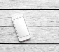 White smart phone on white wooden desk Stock Photos