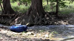 River or stream flowing with kayak on side Stock Footage