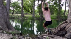 Man does a flip off a rope swing in lake Stock Footage