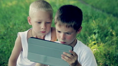 Children close up in the park playing on a tablet  HD 1080p Stock Footage