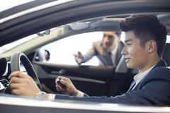 Young businessman taking a test drive - stock photo