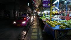 POV walk along night market, sidewalk, cars drive, vegetable stalls, some people Stock Footage