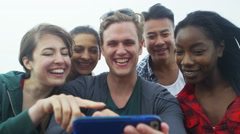 4k Happy mixed ethnicity group of friends looking at mobile phone on the beach - stock footage