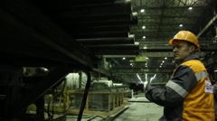 Stock Video Footage of Workers at the factory in the helmet apart the metal pipe