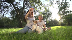 Mom with teen son in the Park with a very cute puppy Jack Russell Terrier fun Stock Footage