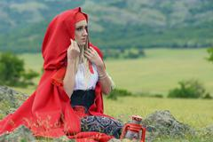 Beautiful blonde woman in old-fashioned dress and red cloak sitting on the me Stock Photos