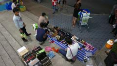 Street vendor sell cheap shoes at stairs, night time, view from behind top - stock footage