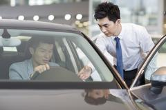 Young man taking a test drive - stock photo