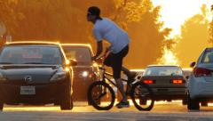 Street traffic cars and bicycle riders in beautiful sunset light. Slow motion - stock footage