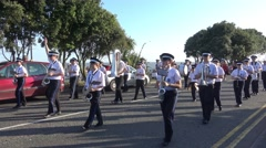 A Marching Band of Young People Walk Along a Road, with Audio Stock Footage