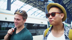 4k 2 Young men travelling together at train station. Friends or young gay couple Stock Footage