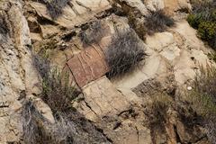 Dry wild grass growing amid jumble of orange granite rocks Stock Photos