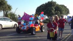 A Mascot Waves to the Crowd as He Drives Along in an Old Fashioned Automobile Stock Footage