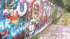 Graffiti Wall in Austin, Texas, MCU moving down wall, some trash in front Stock Footage
