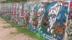 Graffiti wall in Austin, Texas with pictures, over to WS of more walls Stock Footage