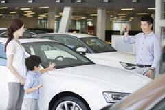 Young family buying car in showroom Kuvituskuvat