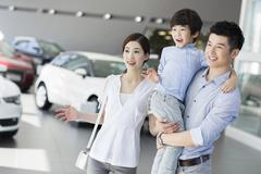 Young family looking at new car in showroom Stock Photos