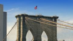 Brooklyn bridge detail tower American flag blue sky New York City NYC Stock Footage