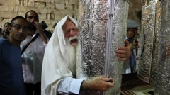 A very old rabbi hugs and kisses Bible Torah scroll inaugurated in Western Wall - stock footage