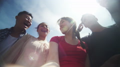 4k Low angle view looking up of happy mixed ethnicity friends posing for selfie Stock Footage