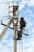 Electrician connects metal parts ground loop on a pole transmission line Stock Photos