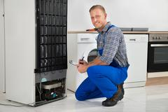 Young Plumber Writing On Clipboard In Front Of Refrigerator Appliance In Kitc Stock Photos