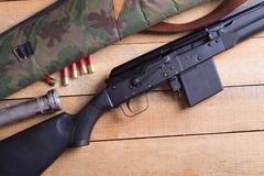 Ammunition , flashlight , & rifle ( gun ) on wooden background Stock Photos
