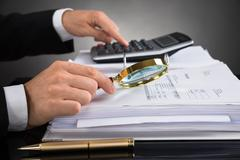 Close-up Of Businessperson Hands Checking Invoice With Magnifying Glass At De Stock Photos