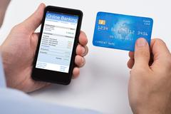 Close-up Of Person With Credit Card And Mobile Phone Doing Online Banking Stock Photos