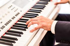 Making music. hand  playing the piano Stock Photos