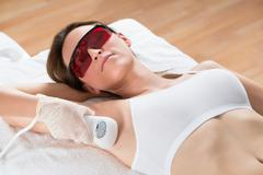 Beautician Removing Hair Of Young Woman's Armpit With Epilator Stock Photos