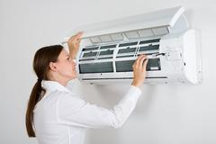 Young Businesswoman Checking Air Conditioner Mounted On Wall In Office Stock Photos