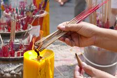 The woman is incensing bundle of joss stick - stock photo