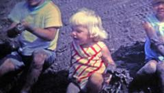 1969: Kids playing in mud made from construction project. Stock Footage