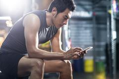 Young man using smart phone in gym Stock Photos