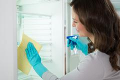 Close-up Of Young Woman Wearing Blue Glove And Cleaning Refrigerator - stock photo