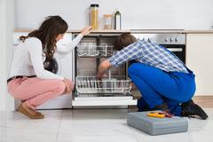 Young Woman Looking At Repairman Repairing Dishwasher In Kitchen Stock Photos