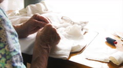 An elderly woman embroidering by the window. Stock Footage