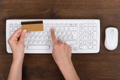 Close-up Of Person Hands With Credit Card And Computer Keyboard At Desk - stock photo