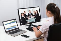 Businesswoman Videoconferencing With Colleagues On Computers At Desk Kuvituskuvat