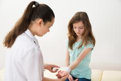 Female Doctor Bandaging Hands Of Girl Child In Clinic Stock Photos