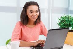 Pretty mulatto girl working on computer Stock Photos