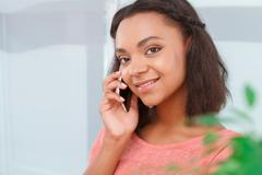 Close-up of mulatto girl talking per mobile phone - stock photo