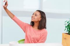 Pretty mulatto woman doing selfie - stock photo